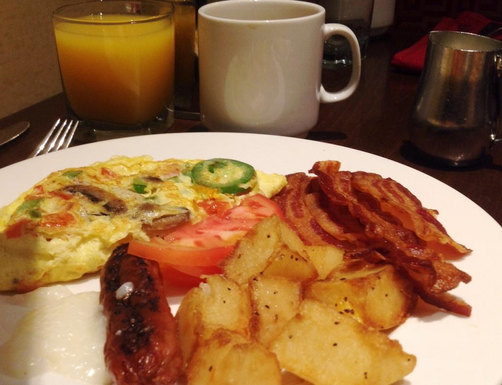 Breakfast in America: omelette, crispy bacon, sausage, tomato, breakfast potatoes and grits.